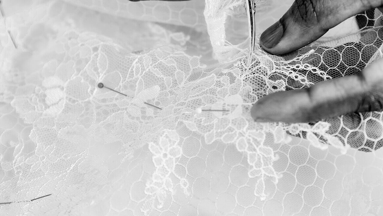 Bridal designer creating an applique with chantilly lace and tulle. tulle and chantilly lace have been pinned and the bridal designer has an embroidery scissors in her right hand.