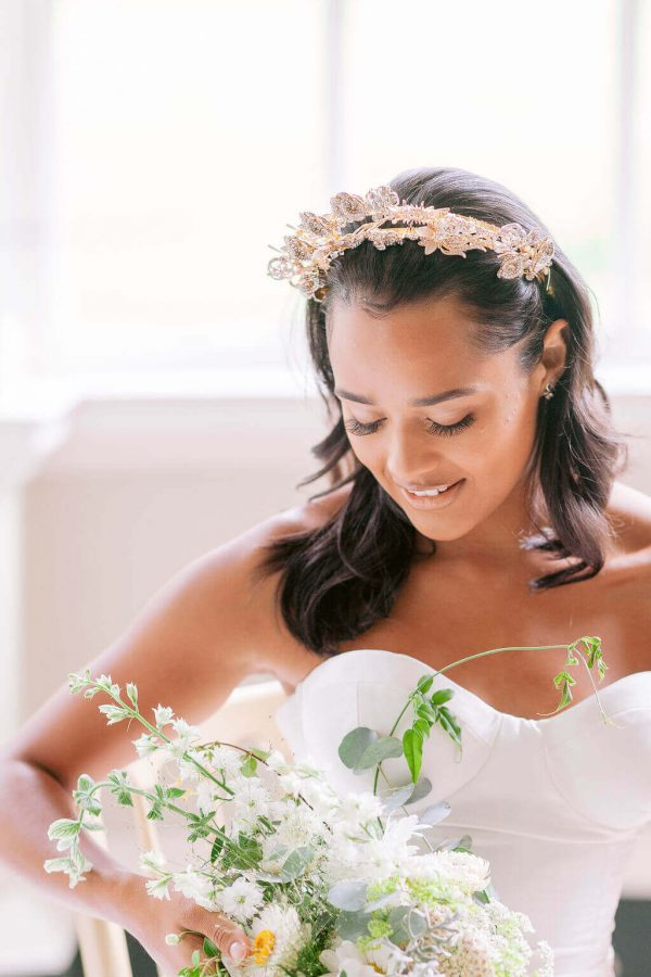 Bride in a luxury bespoke gown with gold headpiece on. bride is smiling and looking down at a predominantly white and green bouquet