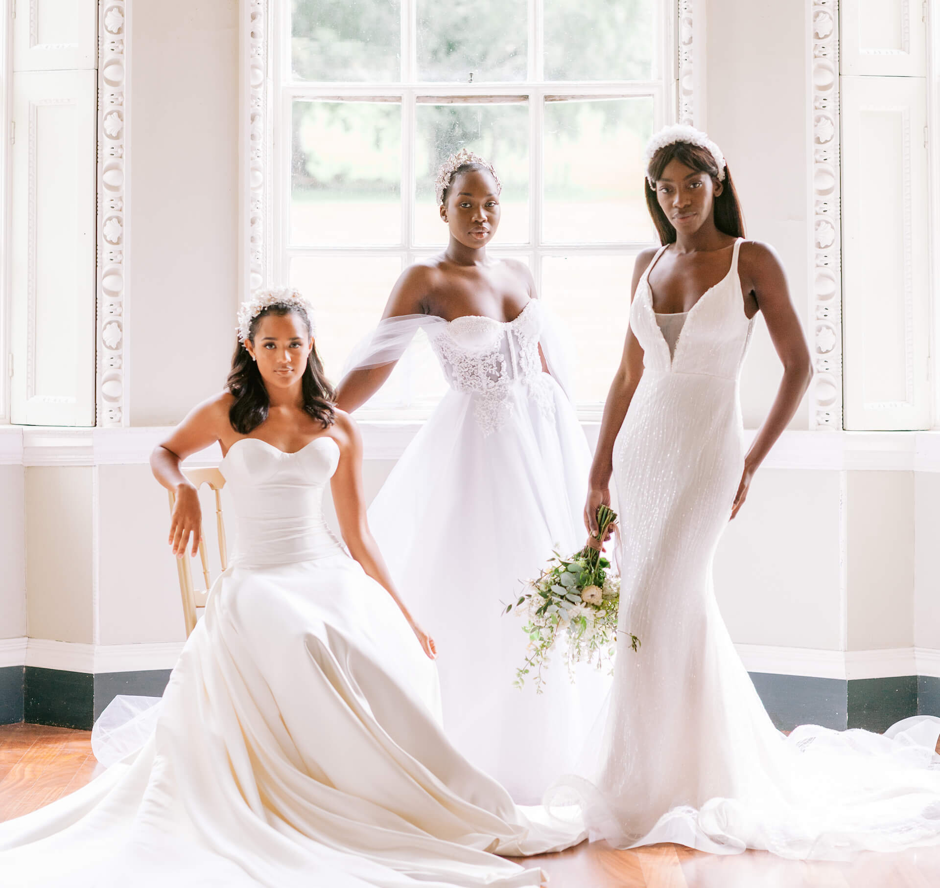 three brides wearing beautifully handcrafted bridal couture pieces with headpieces. the bride on the left is seated on a chair, the bride in the middle is holding on to the chair and the bride on the right is elegantly posed with a bouquet in her right hand. behind them is a large vertical window.