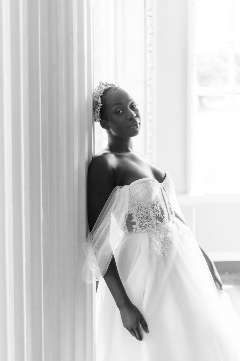 Black Bride is wearing a Felisiti Greis bespoke wedding dress. She is leaning against a white pillar in the gallery room of newburgh priory. In the background is a blurred window.
