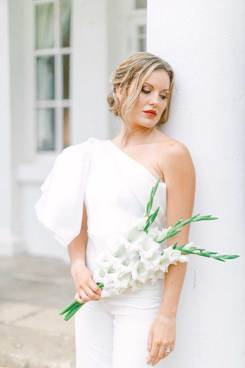 York Bride is wearing a Felisiti Greis bespoke bridal jumpsuit. She is leaning against a white pillar in bawtry hall. She has a bouquet in her right hand. in the background is a blurred window.