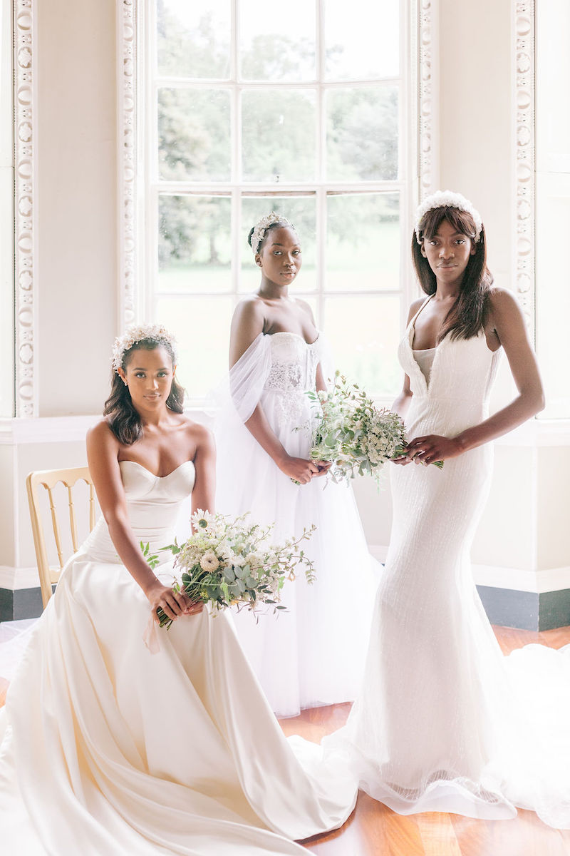 Three brides wearing Felisiti Greis bespoke wedding dresses. they have bouquet in their hands. one is sitting and the other two are standing. in the background is a wide window with natural light shing through.