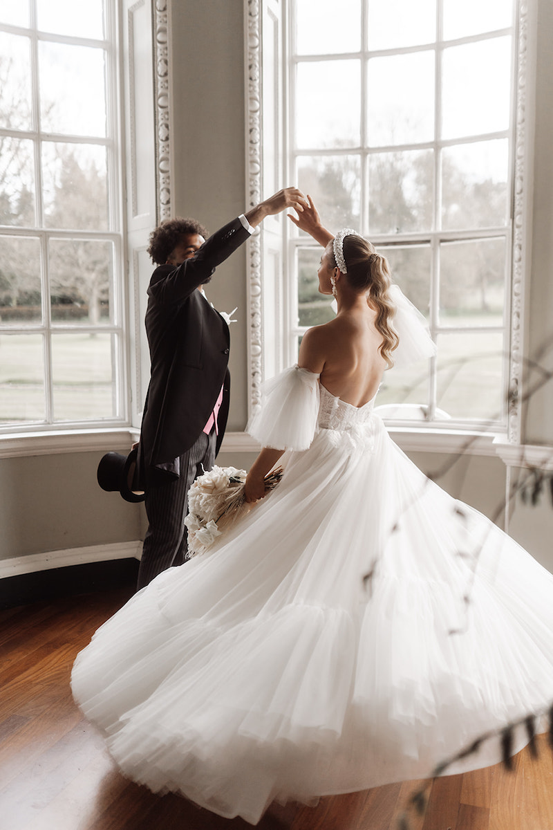 Bride wearing a Felisiti Greis bespoke wedding dress. She is dancing in the gallery room of Newburgh Priory with her groom. in the background is a window with sun shining through.