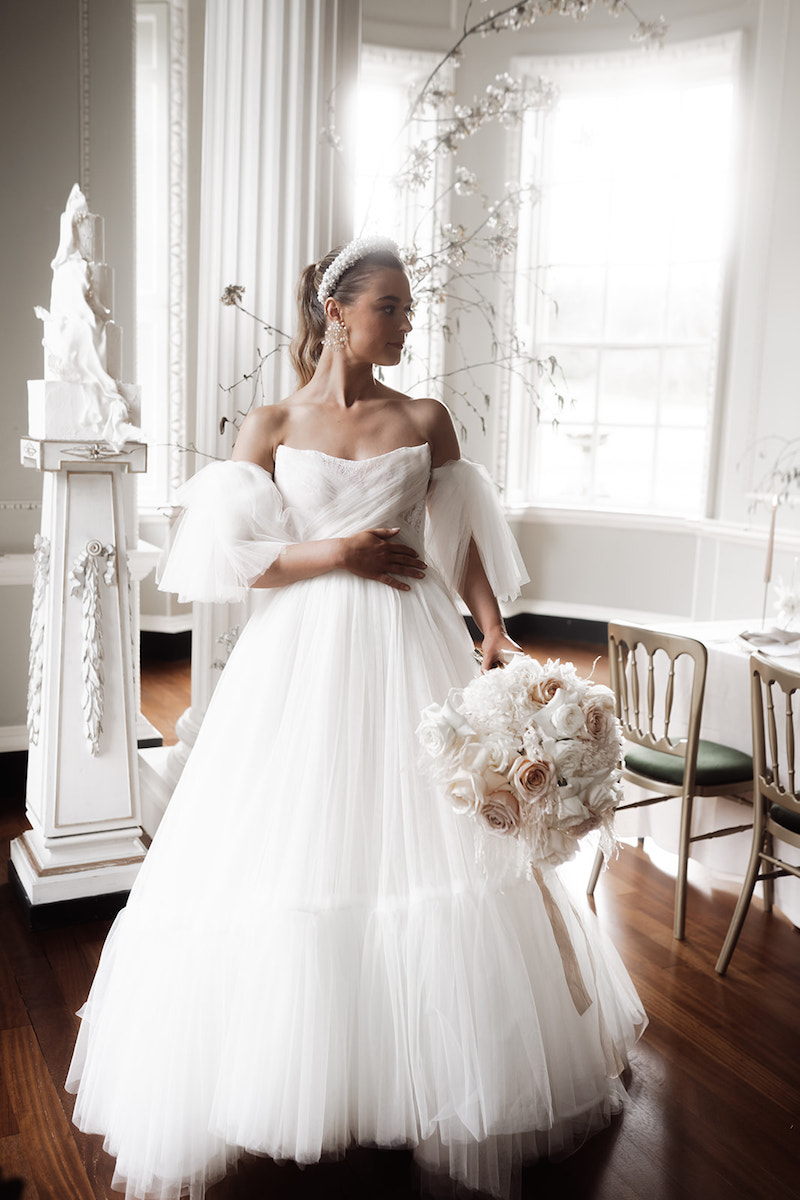 Bride wearing a Felisiti Greis bespoke wedding dress. She is standing inside a stately home. She has her right hand on her waist and a bouquet in her left hand. she has tilted her head slightly to the left, looking away. in the background is a window with sun shining through and a 4 tier white cake on a white pillar.