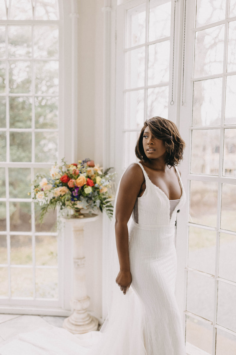 Boston, massachusetts Bride wearing a Felisiti Greis bespoke wedding dress. She is standing infront of a wide window in a stately home. In the background is a window with sun shining through.