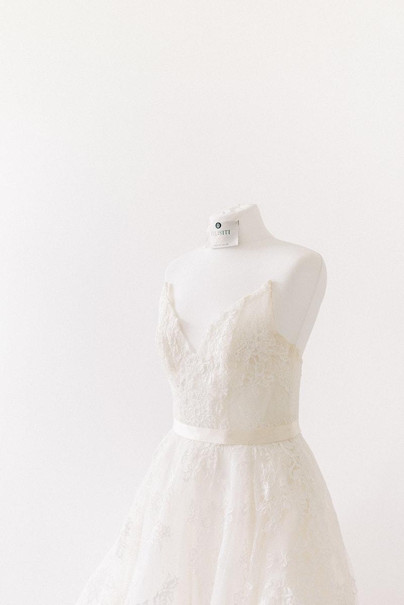 A Felisiti Greis Bespoke wedding dress on a dress form. the background is plain white.
